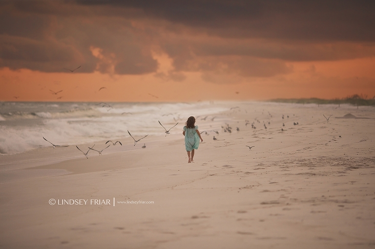 little girl running into seagulls during the sunet on Pensacola Beach